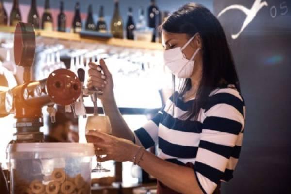 Woman in mask working a coffee machine