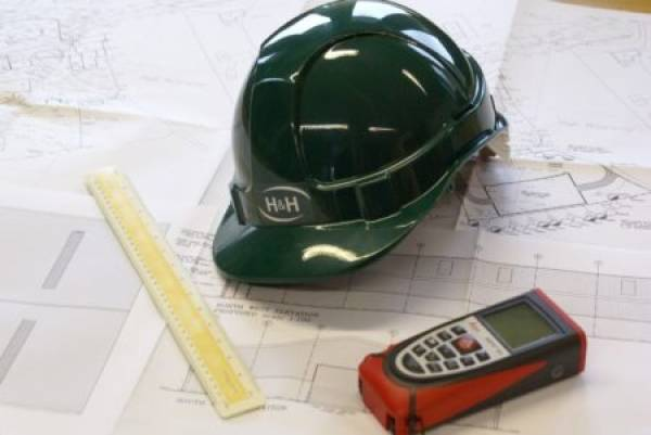 Hard hat and site plans on a table