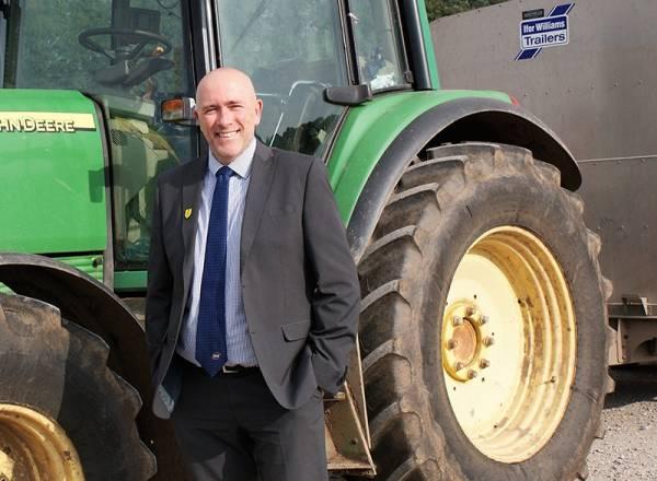 Paul Graham standing next to John Deer Tractor