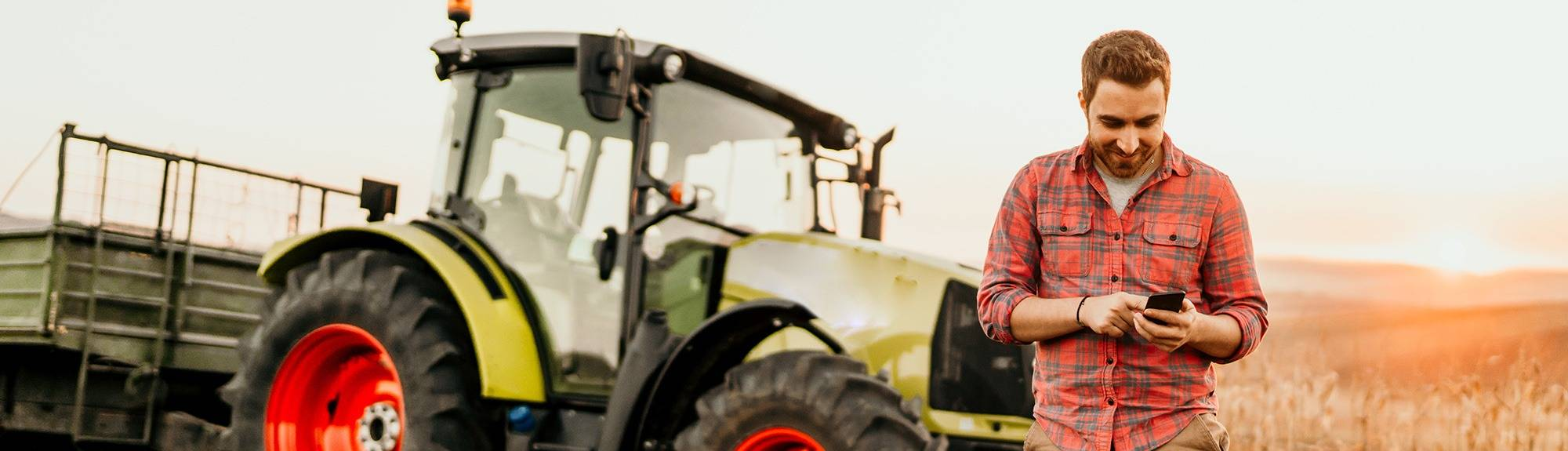 Farmer standing next to tractor in a field on his mobile phone