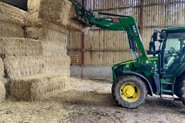 Tractor lifting bales in barn
