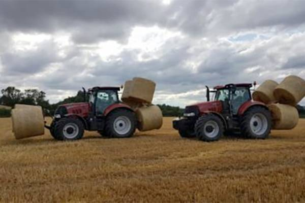 Two tractors carrying bales across a field